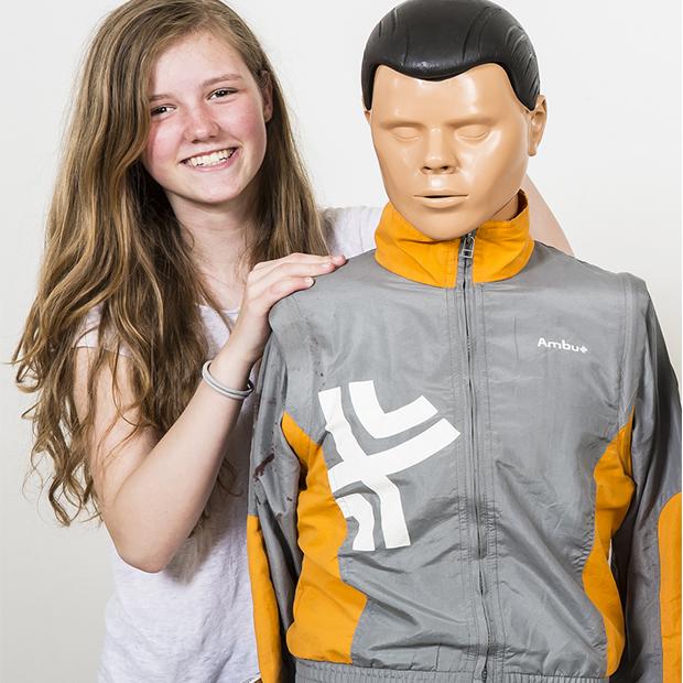 Førstehjælps hold. Billede af pige der står med en førstehjælpsdukke